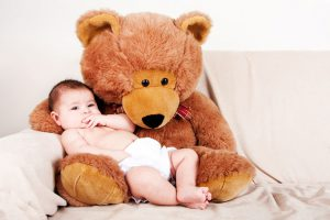 Cute Caucasian Hispanic unisex baby in arms of a big brown stuffed teddy bear sitting on couch.